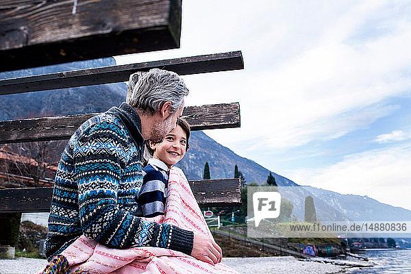 Junge und Vater eingewickelt in eine Decke am Seepier  Seitenansicht  Comer See  Onno  Lombardei  Italien