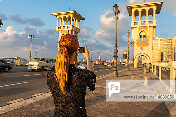 Female tourist with red hair photographing Stanley bridge  rear view  Alexandria  Egypt