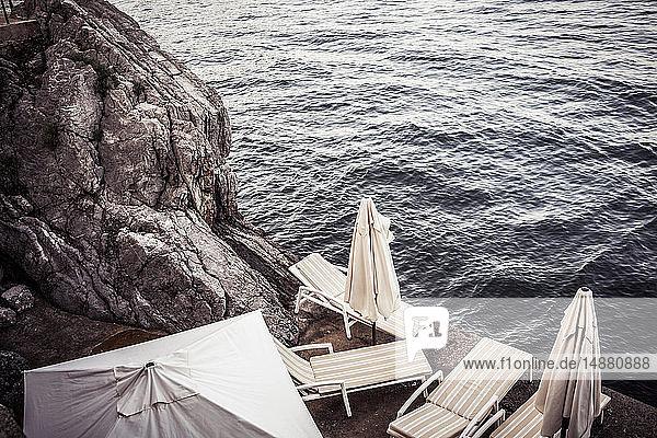 Leere Liegestühle an der felsigen Küste  Hochwinkelansicht  Lovran  Primorsko-Goranska  Kroatien
