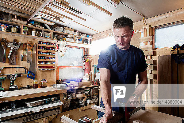 Craftsman preparing parts for wooden object