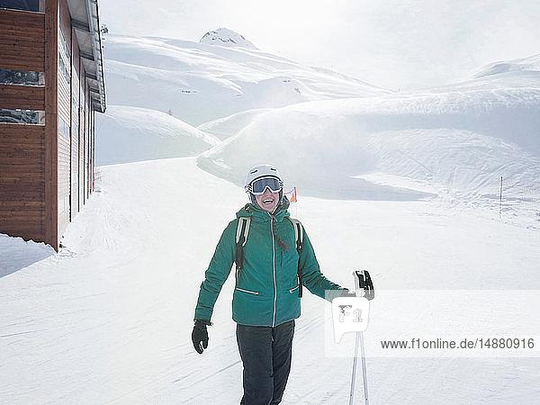 Junge Skifahrerin mit Helm und Skibrille lacht in schneebedeckter Landschaft  Porträt  Alpe Ciamporino  Piemont  Italien
