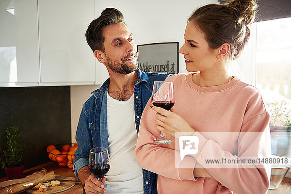 Couple talking and drinking red wine in kitchen