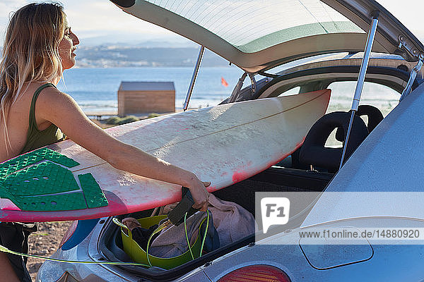 Junge Frau entfernt Surfbrett aus dem Kofferraum