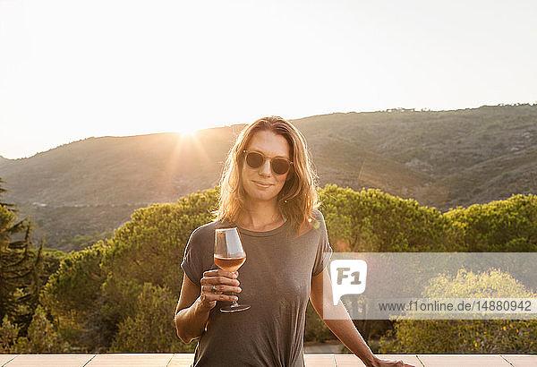 Reife Frau hält ein Glas Wein bei Sonnenuntergang  Porträt  Portoferraio  Toskana  Italien