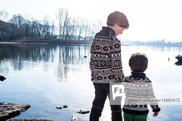 Junge und kleiner Bruder in passenden Pullovern am Seeufer stehend  Comer See  Lecco  Lombardei  Italien