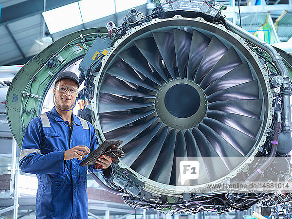 Zusammengesetztes Bild eines Ingenieurs mit Strahltriebwerk in einer Flugzeugwartungsfabrik