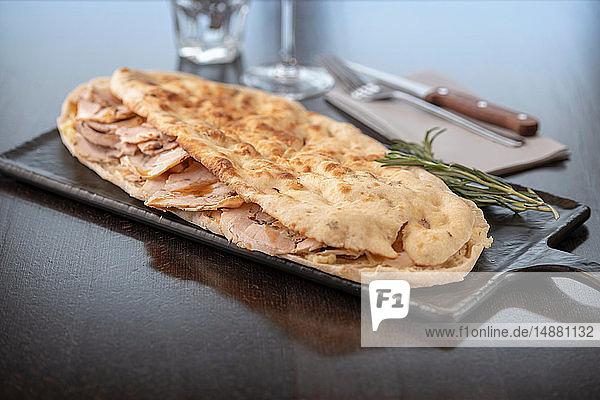Mit Schinken gefüllte Pinsa im italienischen Restaurant