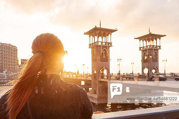 Female tourist with red hair looking out over Stanley bridge at sunset,  rear view,  Alexandria,  Egypt