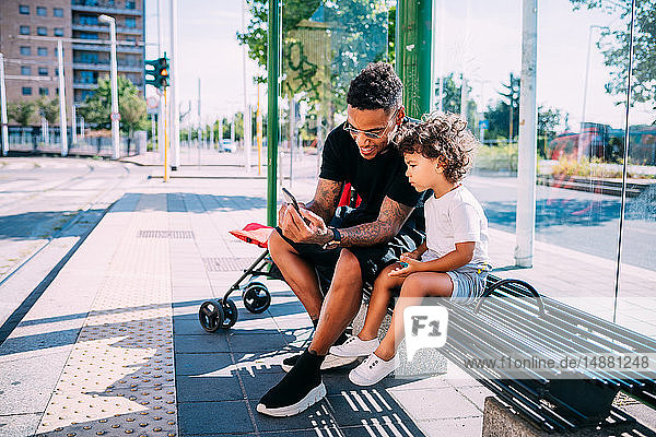 Father teaching son use smartphone on bench