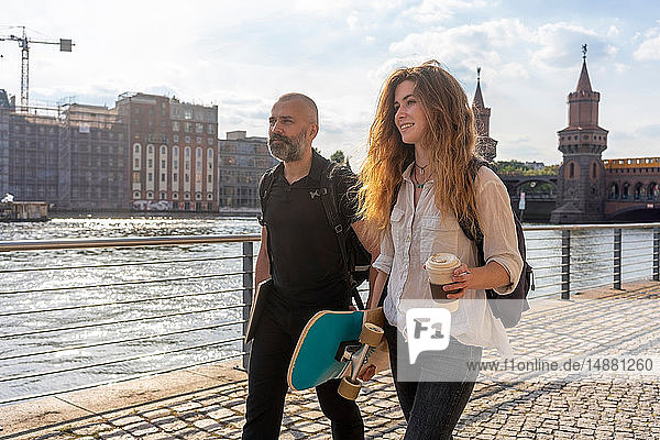 Man and female friend with skateboard on bridge  river  Oberbaum bridge and buildings in background  Berlin  Germany