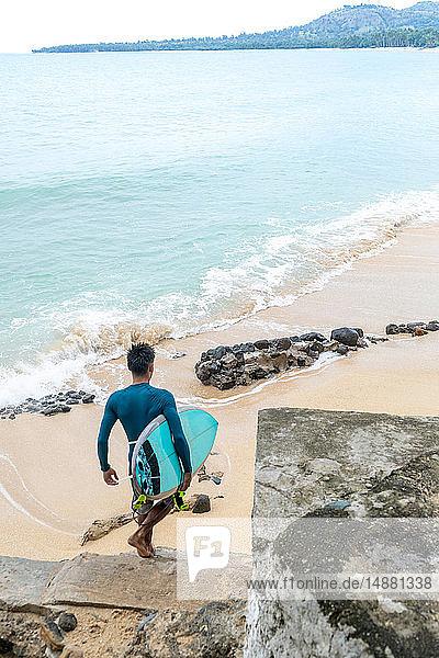 Surfer with surfboard on beach  Pagudpud  Ilocos Norte  Philippines