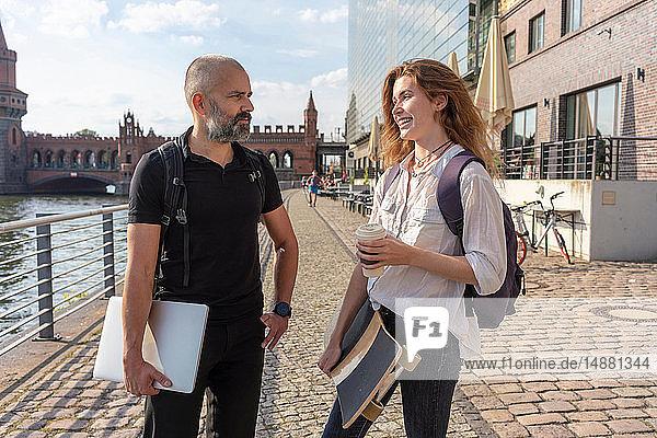 Mann im Gespräch mit einer Freundin mit Skateboard auf Brücke  Fluss  Oberbaumbrücke und Gebäuden im Hintergrund  Berlin  Deutschland