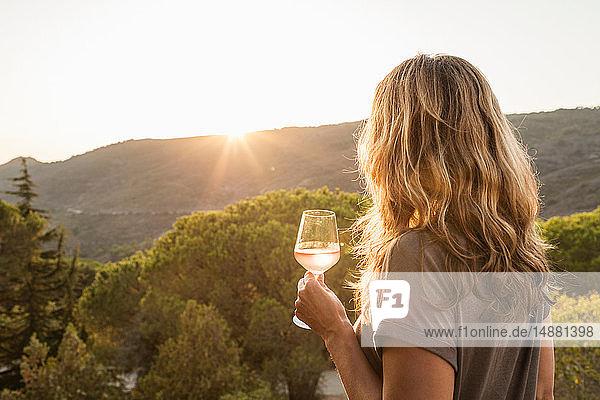 Reife Frau hält ein Glas Wein und betrachtet den Sonnenuntergang über den Hügeln  Rückansicht  Portoferraio  Toskana  Italien