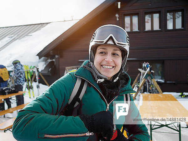 Young female skier wearing helmet and ski goggles sitting at table  Alpe Ciamporino  Piemonte  Italy