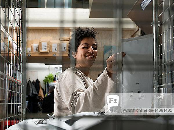 Frau hält Kuriertasche hinter verkabeltem Fenster