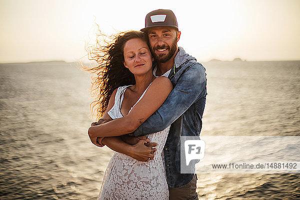 Romantisches Paar,  das sich an der Küste umarmt,  Porträt,  Santa Teresa Gallura,  Sardinien,  Italien