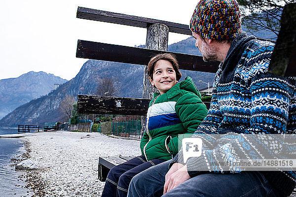 Junge und Vater sitzen plaudernd am Pier des Comer Sees  Comer See  Onno  Lombardei  Italien