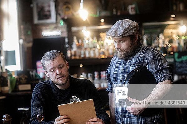 Barman serving customer looking at menu in traditional Irish public house
