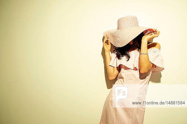 Frau mit Hut,  der das Gesicht verdeckt