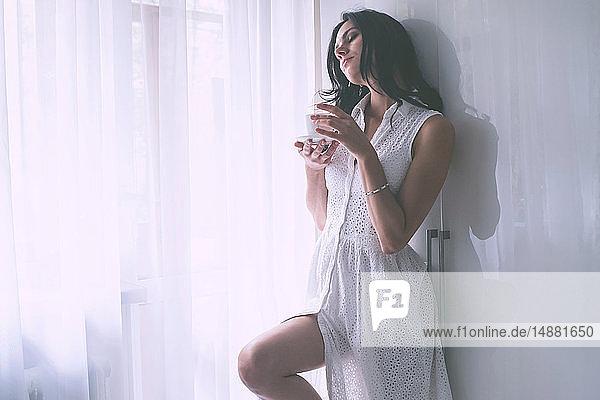 Woman in summer dress beside window