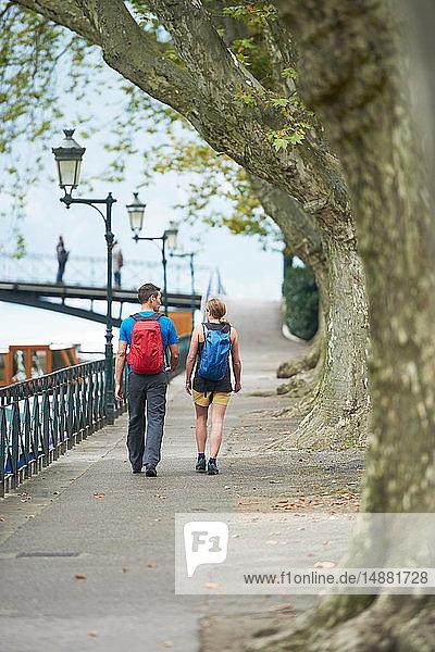 Ein reifer Mann und eine junge Frau spazieren am Flussufer  Rückansicht  Annecy  Rhône-Alpes  Frankreich