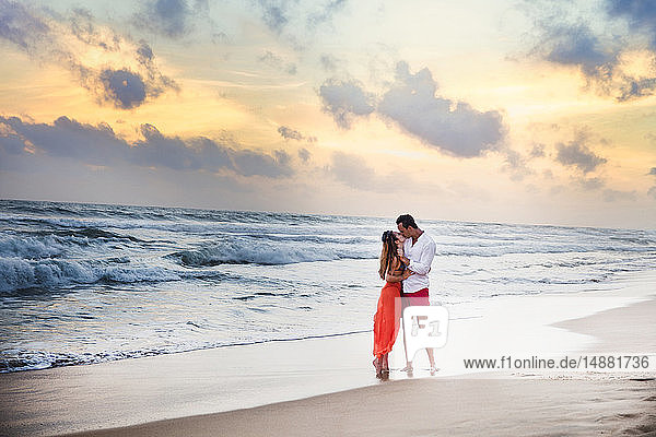 Young couple kissing on beach at sunset,  Hikkaduwa,  Southern,  Sri Lanka