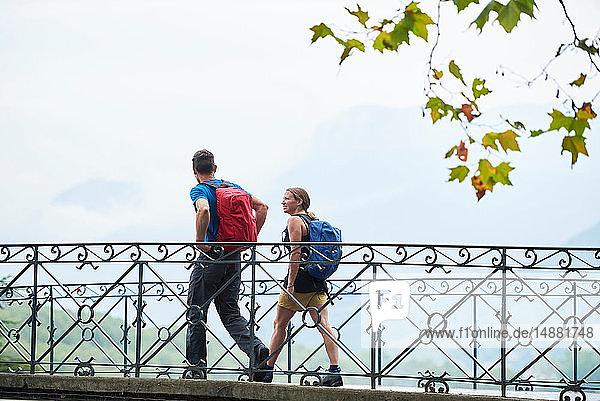 Mann und junge Frau beim Spaziergang über den Flusssteg  Porträt  Annecy  Rhône-Alpes  Frankreich