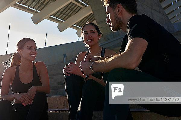 Freunde sprechen über Stufen im Sportstadion