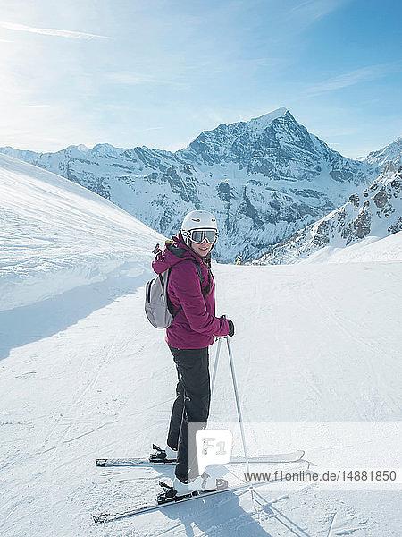 Junge Skifahrerin mit Helm und Skibrille beim Rückblick in verschneiter Landschaft  Porträt  Alpe Ciamporino  Piemont  Italien