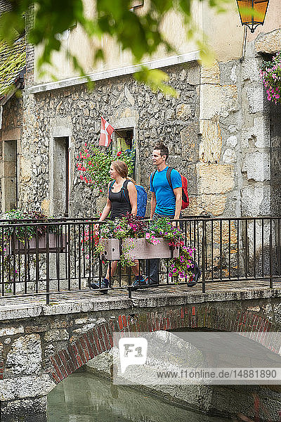 Reifer Mann und junge Frau überqueren Flussbrücke  Annecy  Rhône-Alpes  Frankreich