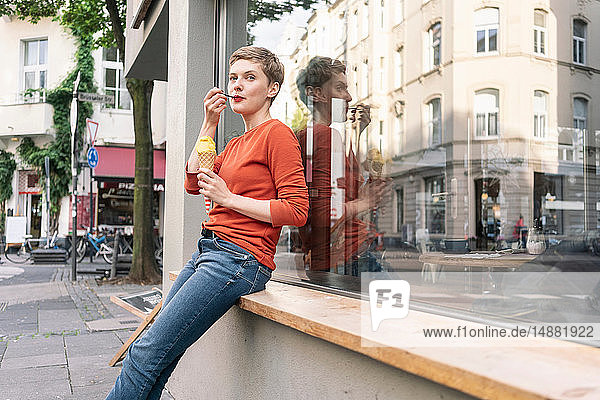 Woman eating ice cream in front of shop  Cologne  Nordrhein-Westfalen  Germany