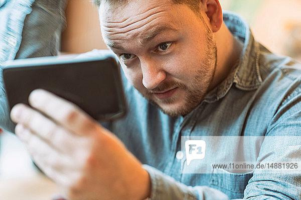 Man using cellphone as mirror