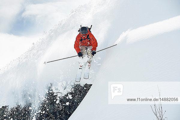 Männlicher Skifahrer fährt in der Luft einen schneebedeckten Berg hinunter  Alpe-d'Huez  Rhône-Alpes  Frankreich