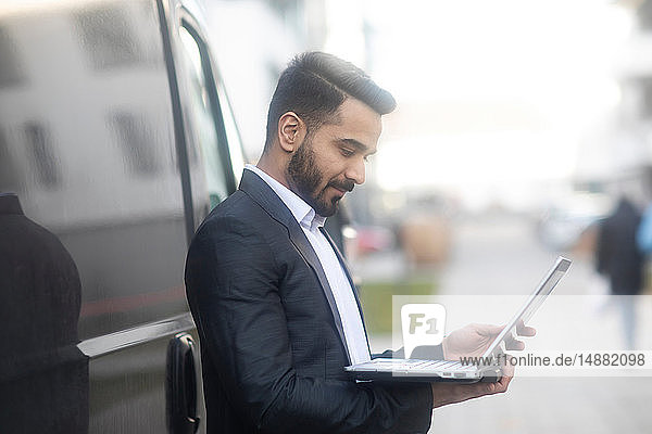 Businessman using laptop by car