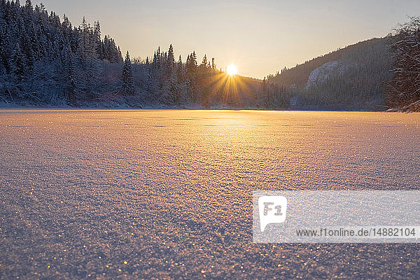 Snow covered lake and forest at sunset