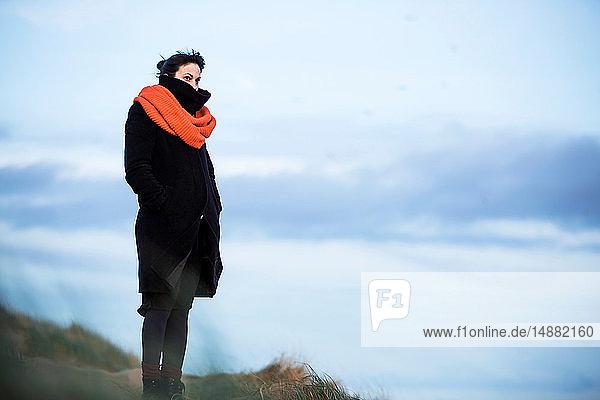Frau schaut am Strand aufs Meer hinaus