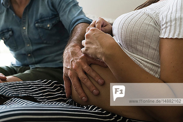 Schwangeres Paar fühlt sich auf dem Sofa bäuchlings