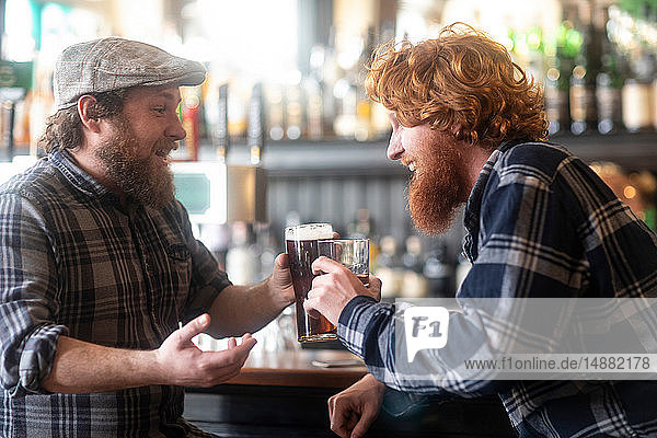 Two male customers making a toast in traditional Irish public house