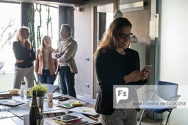 Geschäftsfrau mit Smartphone im Büro  Kollegen im Hintergrund