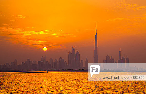 Orange leuchtender Himmel spiegelt sich im Meer wider  Dubai  VAE