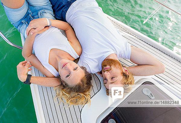 Junges Paar auf einem Segelboot auf dem Chiemsee liegend  Überkopfporträt  Bayern  Deutschland Junges Paar auf einem Segelboot auf dem Chiemsee liegend, Überkopfporträt, Bayern, Deutschland