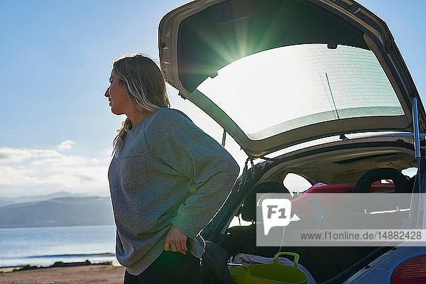 Junge Frau steht hinter offenem Kofferraum
