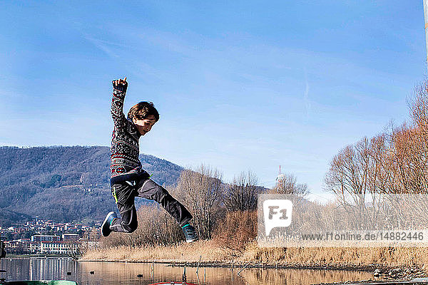 Junge springt mitten in der Luft am Seeufer  Comer See  Lecco  Lombardei  Italien