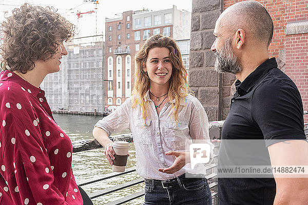 Man and female friends talking  river and buildings in background  Berlin  Germany