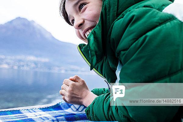 Junge in grünem Anorak auf einer Picknickdecke am Seeufer liegend  beschnitten  Comer See  Onno  Lombardei  Italien