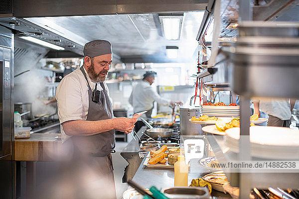 Koch liest Bestellung in der italienischen Restaurantküche