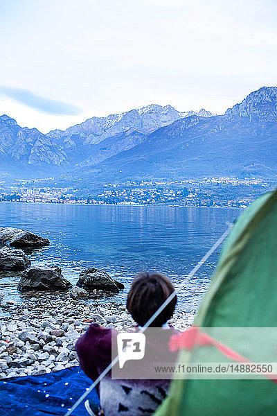 Junge blickt vom Zelt aus auf den See  Rückansicht  Comer See  Onno  Lombardei  Italien