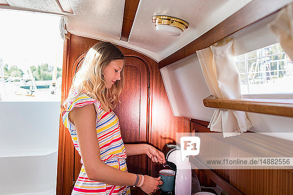Young woman in sailboat cabin using coffee machine