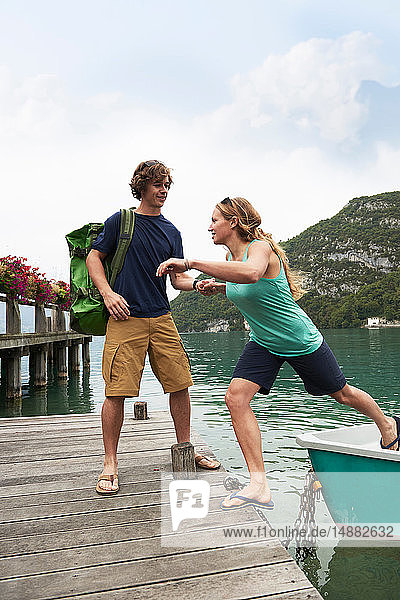 Junges Paar steigt vom Ruderboot auf den Steg  Annecy-See  Annecy  Rhône-Alpes  Frankreich