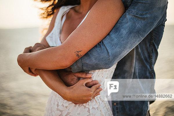 Romantisches Paar umarmt sich an der Küste  Mittelabschnitt  Santa Teresa Gallura  Sardinien  Italien